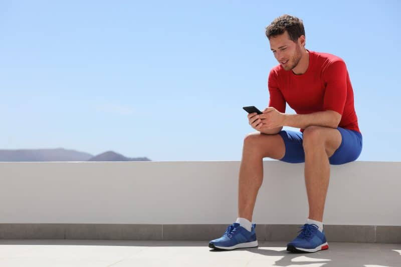 Athlete man watching video on phone screen at home or outdoor gym