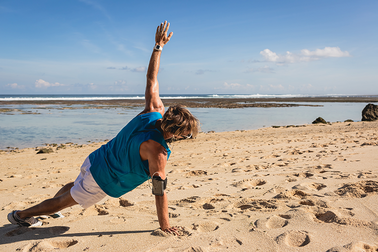 man doing side plank on beach